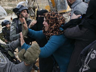 Perempuan Palestina terlibat cekcok dengan polisi Israel saat memprotes pembongkaran rumah di Desa Al-Dirat, dekat kota Hebron, Tepi Barat (16/1/2020). Pembongkaran itu menurut otoritas Israel dilakukan karena rumah dibangun tanpa izin. (AFP/Hazem Bader)