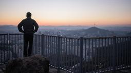 Seorang pejalan kaki melihat pemandangan kota Seoul dan menara Namsan selama matahari terbit di Korea Selatan (31/10). Kota ini adalah pusat politik, budaya, sosial dan ekonomi di Korea Selatan dan Asia Timur. (AFP Photo/Ed Jones)