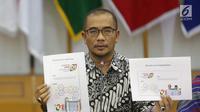 Komisioner KPU Hasyim Asy'ari menunjukkan desain pasangan capres nomor urut 01 saat rapat di Gedung KPU, Jakarta, Senin (29/10). Rapat membahas Penyampaian dan Penetapan Desain Alat Peraga Kampanye (APK). (Liputan6.com/Angga Yuniar)