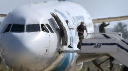Sandera mengangkat tangan saat menuruni pesawat EgyptAir setelah dibebaskan pelaku, Siprus, Selasa (29/3). Pelaku yang diketahui bernama Seif Eldin Mustafa (27) menyerahkan diri dan membebaskan 5 sandera. (Reuters/Yiannis Kourtoglou)