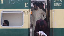 Seorang wanita menyerahkan anaknya kepada pria sebelum naik kereta untuk melakukan perjalanan pulang untuk merayakan Idul Fitri di sebuah stasiun kereta api di Lahore (2/6/2019). Muslim di seluruh dunia bersiap untuk merayakan Idul Fitri yang menandai akhir bulan puasa Ramadan. (AFP Photo/Arif Ali)