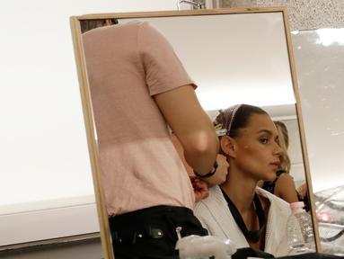Seorang model saat ditata rambutnya di belakang panggung sebelum presentasi busana koleksi Spring-Summer 2018 Versace di Milan, Italia (17/6). Presentasi Spring-Summer 2018 Versace merupakan bagian dari Milan Fashion Week. (AP Photo/Antonio Calanni)