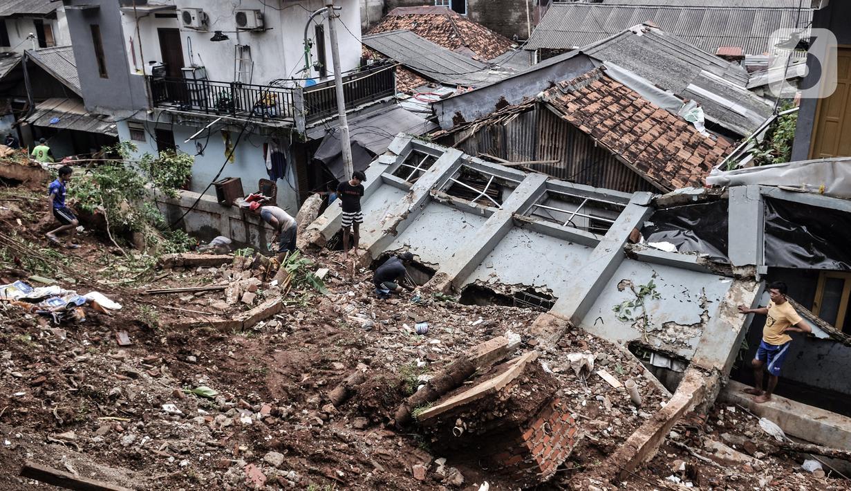 Warga membersihkan puing reruntuhan bangunan pascatanah longsor di kawasan Kemang Timur XI, Jakarta Selatan, Minggu (21/2/2021). Tanah longsor yang berasal dari bangunan rumah elite tersebut terjadi pada Sabtu (20/2) dini hari. (merdeka.com/Iqbal S. Nugroho)