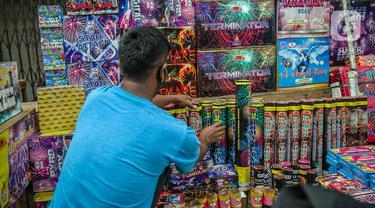 Seorang pedagang menata kembang api di Pasar Asemka, Jakarta, Selasa (29/12/2020). Sejumlah pedagang menyatakan, jelang perayaan Tahun Baru 2021 ini penjualan kembang api mengalami penurunan 75 persen dari tahun lalu. (Liputan6.com/Faizal Fanani)
