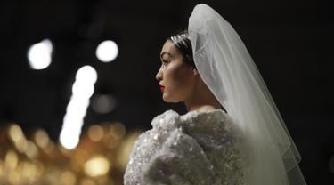 Model Gigi Hadid memakai koleksi Moschino Spring-Summer 2020 selama pekan mode di Milan, Italia (19/9/2019). Gigi tampil anggun dengan sentuhan apik pada balutan gaun pengantin berwarna putih untuk showcase unik yang terinspirasi oleh Alice In Wonderland. (AP Photo/Luca Bruno)