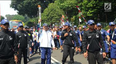 Menteri Komunikasi dan Informatika, Rudiantara (tengah) berlari membawa obor saat kirab obor Asian Games 2018 mengelilingi Kota Bogor, Jawa Barat, Selasa (14/8). Kota Bogor menjadi kota terakhir kegiatan pawai obor Asian Games. (Merdeka.com/Arie Basuki)