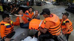 Petugas Basarnas mengevakuasi warga menggunakan perahu karet ketika banjir melanda Perumahan Ciledug Indah 1, Tangerang, Selasa (10/2/2015). Banjir merendam ratusan rumah di kawasan tersebut dengan ketinggian mencapai 90 cm. (Liputan6.com/Andrian M Tunay)