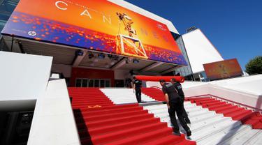 Pekerja memasang karpet merah di depan pintu masuk utama jelang upacara pembukaan Festival Film Cannes 2019 di Cannes, Prancis, Selasa (14/5/2019). Festival Film Cannes merupakan ajang paling bergengsi di dunia perfilman. (REUTERS/Regis Duvignau)
