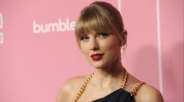 Taylor Swift berpose saat tiba menghadiri Billboard Women In Music 2019 yang digelar oleh YouTube Music di Los Angeles, California (12/12/2019). Taylor Swift cantik memesona dengan jumpsuit biru. (AP Photo/Chris Pizzello)