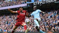 Gelandang Liverpool, Emre Can, berebut bola dengan bek Manchester City, Benjamin Mendy, pada laga Premier League di Stadion Ettihad, Manchester, Sabtu (9/9/2017). City menang 5-0 atas Liverpool. (AFP/Oli Scarff)
