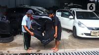 Pekerja mengeluarkan jok mobil yang terkena banjir di bengkel Detailing, Shop, Garage (DSG) di kawasan Pondok Pinang, Jakarta, Kamis (9/1/2020). Biaya yang harus dikeluarkan pemilik mobil berkisar Rp 2 juta hingga Rp 6 juta tergantung tingkat kerusakan kendaraan. (merdeka.com/Arie Basuki)