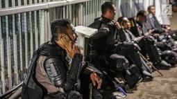 Aparat kepolisan menggunakan telepon genggamnya saat melepas lelah di jembatan penyeberangan orang (JPO) depan Gedung DPR, Jakarta, Selasa (24/9/2019). Mereka melepas lelah usai mengawal demonstrasi mahasiswa menolak pengesahan RUU KUHP dan revisi UU KPK. (Liputan6.com/Faizal Fanani)