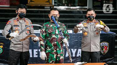 Kapolda Metro Jaya Irjen Fadil Imran (kanan) dan Pangdam Jaya Mayjen Dudung Abdurachman (tengah) menunjukkan barang bukti penyerangan petugas, Polda Metro Jaya, Jakarta, Senin (7/12/2020). Enam dari 10 pengikut Rizieq Shihab tewas ditembak polisi di Tol Jakarta-Cikampek. (Liputan6.com/Faizal Fanani)