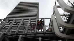 Pekerja melakukan pengerjaan revitalisasi Jembatan Penyeberangan Orang (JPO) Ratu Plaza, Jakarta, Jumat (28/12). JPO Ratu Plaza masuk dalam proses revitalisasi dan ditargetkan selesai pada akhir Desember 2018. (Liputan6.com/JohanTallo)