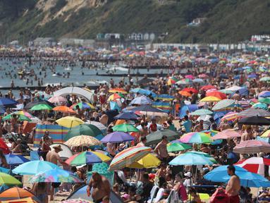 Kerumunan pengunjung berkumpul di pantai untuk menikmati hari terpanas tahun ini di Bournemouth, Kamis (25/6/2020). Para pejabat di Inggris selatan menyatakan keadaan darurat setelah ribuan orang berbondong-bondong menyambangi pantai setempat. (Andrew Matthews/PA via AP)