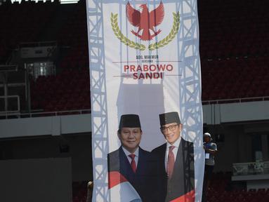Pekerja merapikan poster wajah pasangan capres-cawapres nomor urut 02 Prabowo Subianto-Sandiaga Uno di Stadion Utama Gelora Bung Karno (SUGBK), Jakarta, Sabtu (6/4). Prabowo dan Sandiaga akan melakukan kampanye akbar di stadion GBK pada Minggu 7 April 2019. (merdeka.com/Imam Buhori)