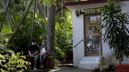 Orang-orang menunggu di luar kantor Western Union sebelum penutup kantor di Havana, Kuba, Senin (23/11/2020). Penutupan yang didorong oleh sanksi keras AS itu akan membuat ribuan warga Kuba yang biasa menggunakan jasa perusahaan pengiriman uang tersebut kehilangan akses. (AP/Ismael Francisco)