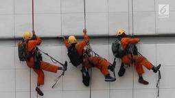 Pemandangan ketika pekerja membersihkan salah satu gedung bertingkat di Bundaran Hotel Indonesia, Jakarta, Rabu (14/3). BPJS Ketenagakerjaan mencatat 123 ribu kasus kecelakaan kerja tercatat sepanjang 2017. (Liputan6.com/Angga Yuniar)