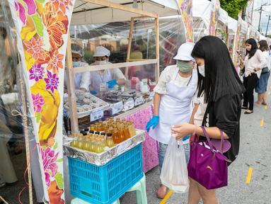 Para penjual menawarkan minuman kepada pelanggan dalam festival kuliner di kota tua Phuket, Thailand (13/9/2020). Festival selama dua hari itu digelar untuk mendorong pariwisata dan perekonomian setempat. (Xinhua/Zhang Keren)