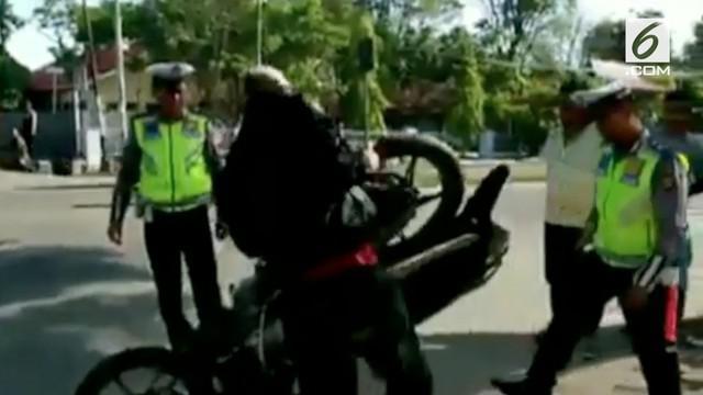 Tak terima ditilang oleh polisi, seorang pengendara membanting motornya sendiri di hadapan petugas.