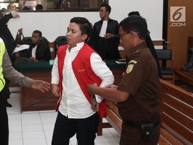 Petugas memborgol Komisaris First Travel Kiki Hasibuan usai menjalani sidang vonis di Pengadilan Negeri Depok, Jawa Barat, Rabu (30/5). Kiki divonis 15 tahun penjara dan denda 5 miliar rupiah subsider 8 bulan penjara. (Liputan6.com/Herman Zakharia)