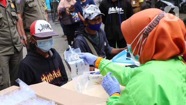 Petugas memberikan kantong kepada warga untuk menjalani tes GeNose C19 usai terjaring razia penggunaan masker di Kelurahan Sudimara Barat, Kota Tangerang, Kamis (27/5/2021). Tes tersebut untuk menekan penyebaran corona COVID-19 di wilayah tersebut. (Liputan6.com/Angga Yuniar)