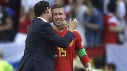 Tangis Sergio Ramos (kanan) pecah saat memeluk pelatih, Fernando Hierro usai kalah dari Rusia pada laga 16 besar Piala Dunia 2018 di Luzhniki Stadium, Moskow, Rusia, (1/7/2018). Spanyol kalah adu penalti 3-4. (AFP/Juan Mabromata)