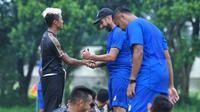 pelatih fisik Arema, Marcos Gonzales sambil bercanda membasuh tangah striker Kushedya Hari Yudo saat awal kabar virus corona menyebar. (Bola.com/Iwan Setiawan)