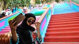 Pengunjung berswafoto dengan latar belakang tangga 272 langkah yang baru dicat, jalan untuk menuju kuil Batu Caves di Kuala Lumpur, 30 Agustus 2018. Pro kontra dialami oleh objek wisata religi yang bersejarah di Malaysia tersebut. (AFP/Manan VATSYAYANA)
