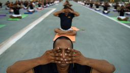 Personel Angkatan Laut India melakukan gaya yoga di atas kapal induk INS Viraat di Mumbai, India, (21/6). PM Narendra Modi mengatakan 21 Juni dirinya dan jutaan orang di seluruh dunia merayakan Hari Yoga Internasional. (AFP Photo/Punit Paranjpe)