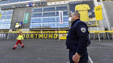 Petugas Keamanan dengan menggunakan masker berjaga di depan Stadion Signal Iduna Park, Jerman, Sabtu (4/4/2020). Stadion Borussia Dortmund ini dialihfungsikan menjadi tempat pusat pengujian COVID-19. (AP/Martin Meissner)