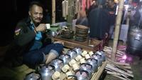 Salah satu pengunjung tengah menikmati hidangan teh hangat dalam festival Nyaneut di Garut (Liputan6.com/Jayadi Supriadin)