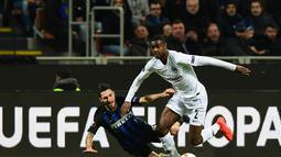 Matteo Politano gagal menghentikan Obie Ndicka pada leg kedua, babak 16 besar Liga Europa yang berlangsung di Stadion Giuseppe Meazza, Jumat (15/3). Inter Milan kalah 0-1 kontra Eintracht Frankfurt. (AFP/Miguel Medina)
