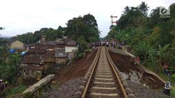 Jalur kereta api tujuan Bogor-Sukabumi longsor terlihat di Kampung Maseng RT02/08, Desa Warung Menteng, Kecamatan Cijeruk, Selasa (5/2). Jenazah korban langsung dibawa ke RSUD Ciawi untuk divisum. (Liputan6.com/Achmad Sudarno)