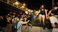 Pengunjuk rasa yang menolak RUU Ekstradisi berhamburan saat bentrok dengan polisi di luar gedung parlemen, Hong Kong, Senin (10/6/2019). Massa diperkirakan akan semakin membesar dalam beberapa hari mendatang. (AP Photo/Kin Cheung)