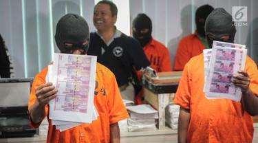 Tersangka menunjukan uang palsu saat gelar rilis sindikat pengedar uang palsu di Pulau Jawa oleh Direktorat Tindak Pidana Ekonomi Khusus Bareskrim Polri di Jakarta, Rabu (18/10). (Liputan6.com/Faizal Fanani)