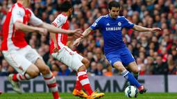 Gelandang Chelsea,  Cesc Fabregas (kanan) berusaha melewati dua pemain Arsenal saat Laga Liga Premier Inggris di Emirates Stadium, Minggu (26/4/2015). Arsenal bermain imbang 0-0 atas Chelsea. (Reuters/Eddie Keogh)