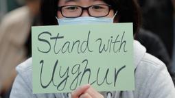 Seorang demonstran memegang kertas bertuliskan dukungan untuk Uighur dan perjuangan mereka terhadap hak azasi manusia di Hong Kong, Minggu (22/12/2019). Demonstran memprotes kebijakan China terkait minoritas Uighur. (AP Photo/Lee Jin-man)