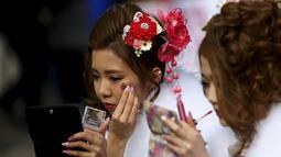 Wanita Jepang berpakaian kimono merias diri sebelum upacara Coming of Age Day (Hari Kedewasaan Nasional) di taman hiburan Tokyo, Senin (11/1). Hari Kedewasaan Nasional ini dirayakan para muda-mudi Jepang yang menginjak usia 20 tahun (REUTERS/Yuya Shino)