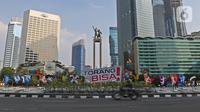 Pengendara sepeda motor melintas di dekat maskot Pekan Olahraga Nasional (PON) XX Papua di Bundaran Hotel Indonesia, Jakarta, Jumat (16/07/2021). Pemasangan maskot PON XX Papua itu bentuk promosi kegiatan pekan olahraga yang diselenggarakan tiap empat tahun sekali. (Liputan6.com/Herman Zakharia)