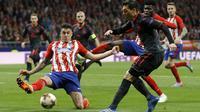 Aksi pemain Arsenal, Mesut Ozil (kanan) melepaskan tembakan saat di adang pemain Atletico, Jose Maria Gimenez pada semifinal Liga Europa di Wanda Metropolitano stadium, Madrid, (3/5/2018). Atletico menang 1-0. (AP/Francisco Seco)