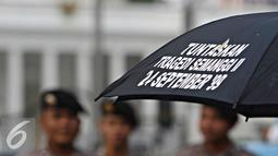 Petugas berjaga saat aksi Kamisan ke-436 di Jakarta, Kamis (24/3). Aksi sekaligus memperingati Hari Internasional untuk Hak atas Kebenaran Terkait Pelanggaran HAM Berat dan Martabat Korban yang jatuh pada 24 Maret. (Liputan6.com/Immanuel Antonius)