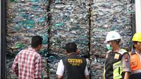 Petugas Bea Cukai serta polisi menunjukkan kontainer berisi sampah plastik di Tanjung Priok, Jakarta, Rabu (18/9/2019). Bea Cukai bekerja sama dengan KLHK dan kepolisian memulangkan sembilan kontainer berisi 135 ton sampah plastik impor bercampur limbah B3 asal Australia. (Liputan6.com/Angga Yuniar)