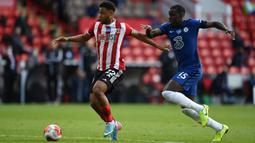 Pemain Sheffield United, Lys Mousset berebut bola dengan bek Chelsea, Kurt Zouma pada pekan ke-35 Liga Inggris di Bramall Lane, Minggu (12/7/2020) dini hari WIB. Chelsea dihajar 0-3 oleh Sheffield United. (Shaun Botterill/Pool via AP)
