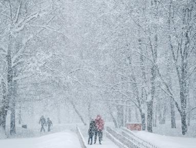 Orang-orang berjalan saat hujan salju turun lebat di dekat museum Kolomenskoye di Moskow (4/2). Hujan salju lebat yang turun semalaman mengakibatkan jalan-jalan dan bangunan di pusat kota dan beberapa daerah di Rusia tertutup salju. (AFP/Yuri Kadobnov)