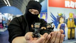 Seorang pria berkostum ninja berpose dengan mainan saat Toy Fair  atau Pameran Mainan tahunan di Olympia, London, Inggris, Selasa (23/1). (AFP PHOTO/Tolga AKMEN)