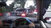 Tangkapan layar aksi polisi menghentikan pengendara mobil sedan yang menerobos razia narkoba di Kota Jambi. (Liputan6.com/@sekitarjambi)