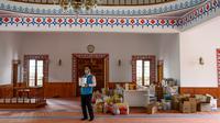 Imam masjid Dedeman, Abdulsamet Cakir (33) membawa barang-barang menuju pintu masjid di distrik Sariyer, Istanbul pada 21 April 2020. Di pintu masuk masjid itu dimana rak-rak yang biasanya diperuntukkan sebagai tempat sepatu jemaah, kini penuh dengan kebutuhan sehari-hari. (Bulent Kilic/AFP)