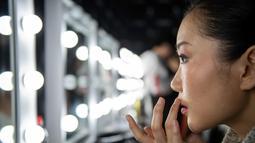 Model merapihkan lipstik dibibirnya sebelum tampil membawakan koleksi Rabbit-Warm karya Zhuang Ganran selama China Fashion Week di Beijing (30/10). (AFP Photo/Nicolas Asfouri)