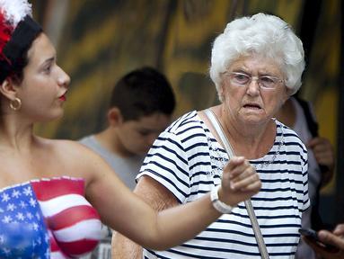 Seorang wanita dengan bertelanjang dada dipinggiran ruas jalan Times Square, New York,AS,  Selasa (18/8/2015). Mereka meminta uang kepada para wisatawan yang ingin mengajak foto bersama dengan tanpa memakai busana. (REUTERS/Carlo Allegri)